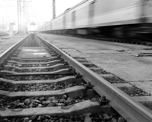 Image of train tracks with a fast train near in black and white